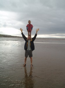 Dad on beach with child on his shoulders
