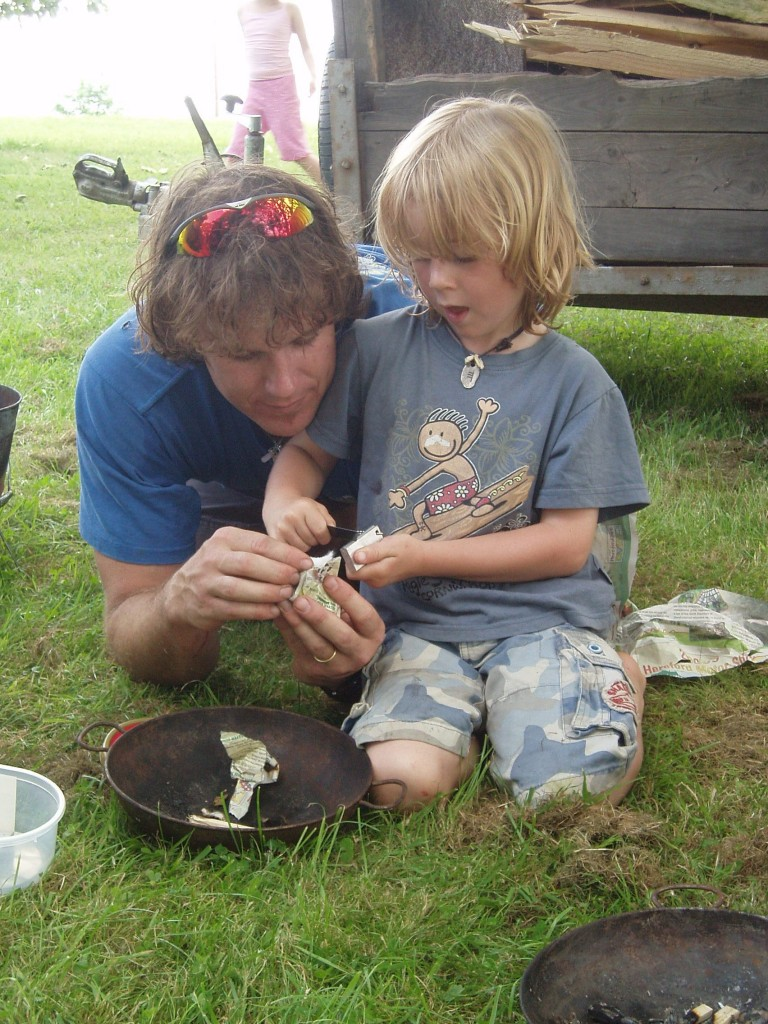 father and son lighting fire with flint