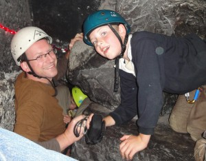 Dad and son squeezing through a cave