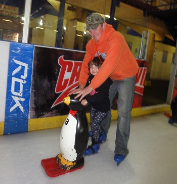 A dad helping his daughter skate round the ice