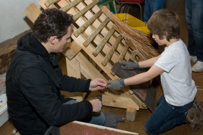 A dad passing a nail to his son for him to secure a tile to a roof section