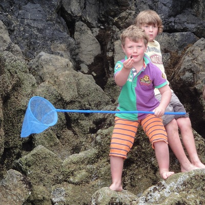 A boy holds a mussel out that he has found by the sea