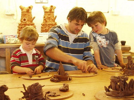 A dad making clay sculptures with his children