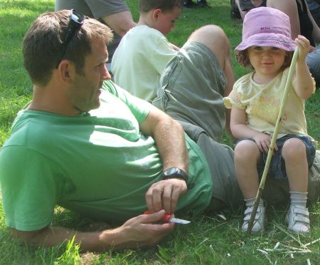 A dad whittles a stick with his young daughter