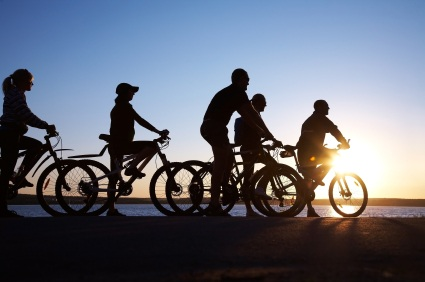 A family cycling at sunset