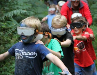 A group of blinfolded children and dads follow an outdoor trail