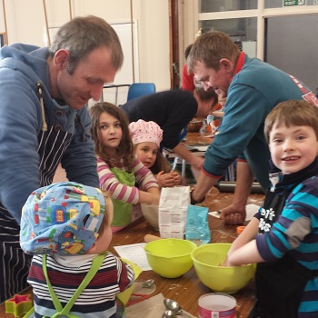 A group of dads and children mix the ingredients for gingerbread men