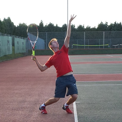 An experienced tennis player in mid-serve