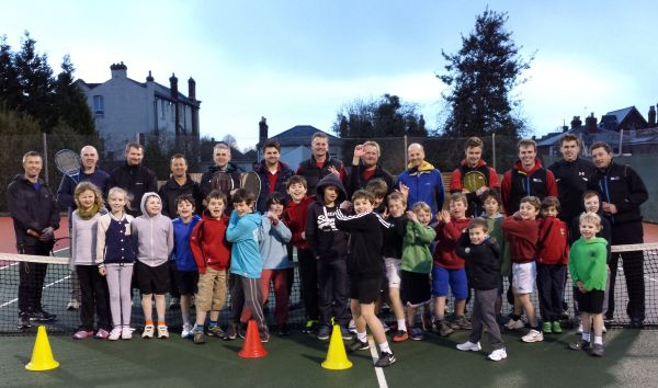Dads and children pose for a group shot after their tennis coaching event