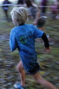 A boy running the 2012 Mudrunner with a 'Days Out With Dad' T-shirt