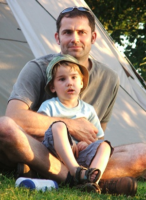 A dad sat on the grass by a tent with a boy